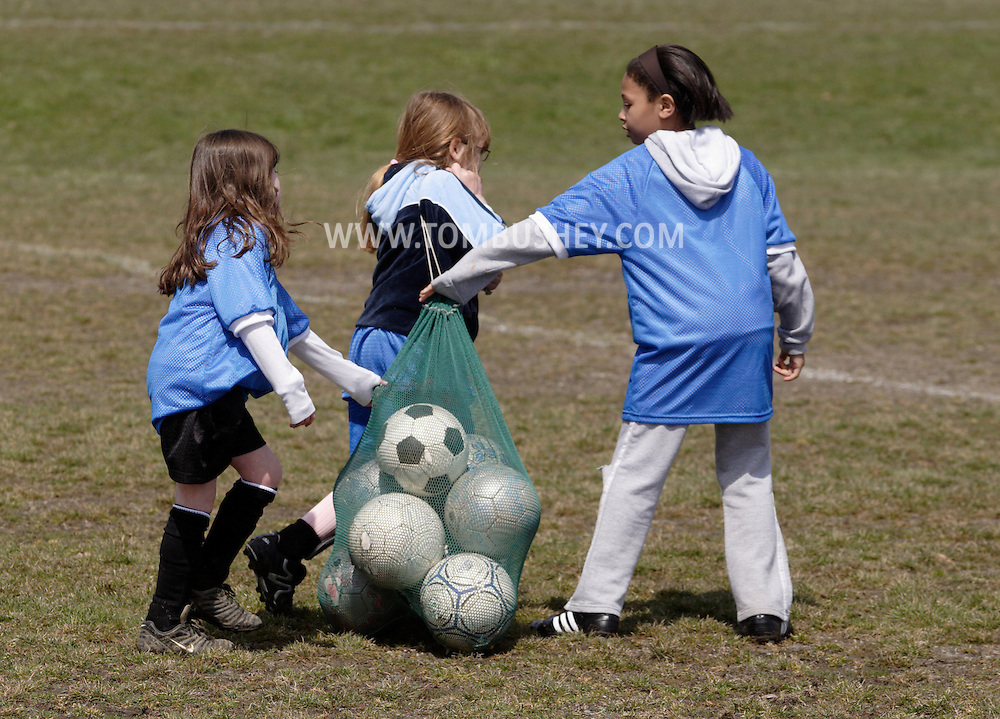 Middletown, NY - Three girls help carry a bag of soccer ball during Middletown Youth Soccer League practice at Watts Park on April 14, 2007..