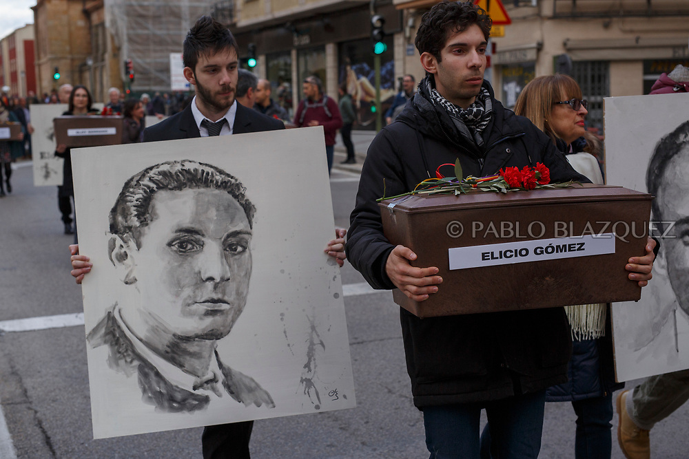 14/04/2018. Grand nephews Alberto (R) and Alvaro (L) Rodriguez carry a coffin containing the remains of victim of Spain Civil War Elicio Gomez and a portrait depicting him along the streets in center of Soria during a homage to hand the remains to their families on April 14, 2018 in Soria, Spain. La Asociacion Soriana Recuerdo y Dignidad (ASRD) 'The Soria Association for Memory and Dignity' celebrated a tribute to hand over the remains of civil war victims to their families. The Society of Sciences of ARANZADI helped with the research, exhumation and identification of the bodies, after villagers passed the information about the mass grave, 81 years after the assassination took place, to the ASRD. Seven people were assassinated around August 25, 1936 by Falangists, as part of General Francisco Franco armed forces, and buried in the 'Fosa de los Maestros' (Teachers Mass Grave) near Cobertelada, Soria, after being taken from prison of Almazan during the Spanish Civil War. Five of them were teachers in the region, and also friends of Spanish writer Antonio Machado. The other two still remain unidentified. Another body was assassinated by Falangists accompanied by a priest in 1936, and was exhumed on 23 September of 2017 near Calata&ntilde;azor, Soria. It belonged to Abundio Andaluz, a politician, lawyer and musician in Soria.<br /> Spain's Civil War took the lives of thousands of people on both sides, and civilians. But Franco continued his executions after the war has finished. Teachers, as part of the education sector, were often a target of Franco's forces. Spanish governments has never done anything to help the victims of the Civil War and Franco's dictatorship while there are still thousands of people missing in mass graves around the country. (&copy; Pablo Blazquez)