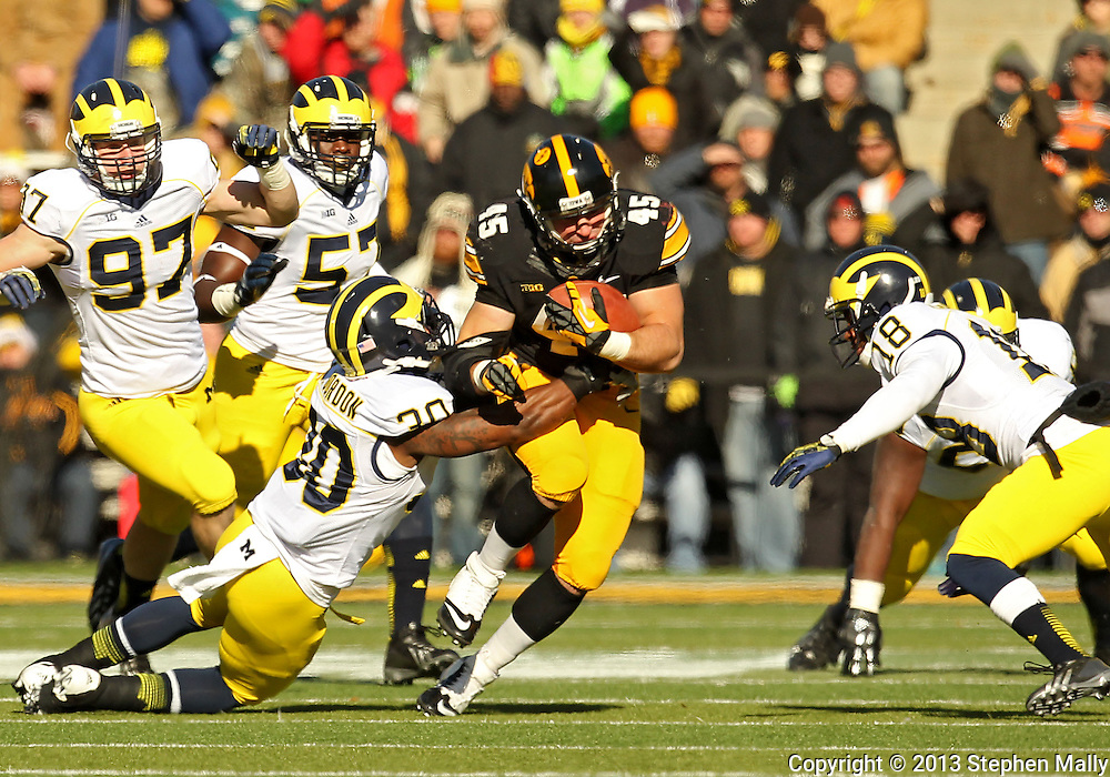November 23 2013: Iowa Hawkeyes running back Mark Weisman (45) tries to bounce off of Michigan Wolverines safety Thomas Gordon (30) on a run during the first quarter of the NCAA football game between the Michigan Wolverines and the Iowa Hawkeyes at Kinnick Stadium in Iowa City, Iowa on November 23, 2013. Iowa defeated Michigan 24-21.