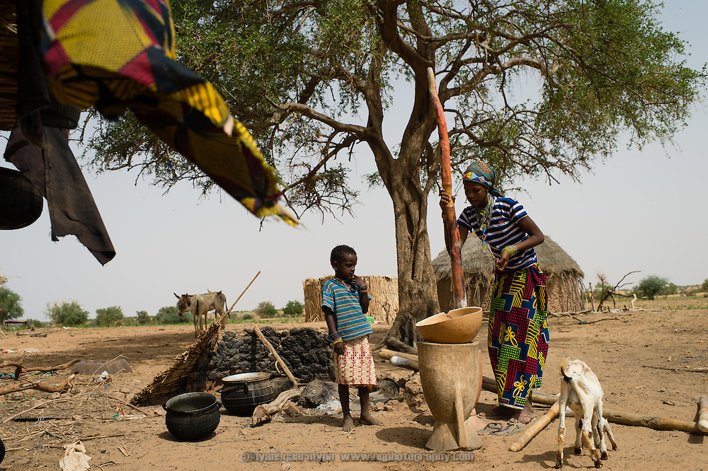 A woman pounding millet as washing blows on a line in a nomadic Fulani encampment in Garinbale in the Commune of Soukoukoutan in the Dosso Region of Niger on 23 July 2013.