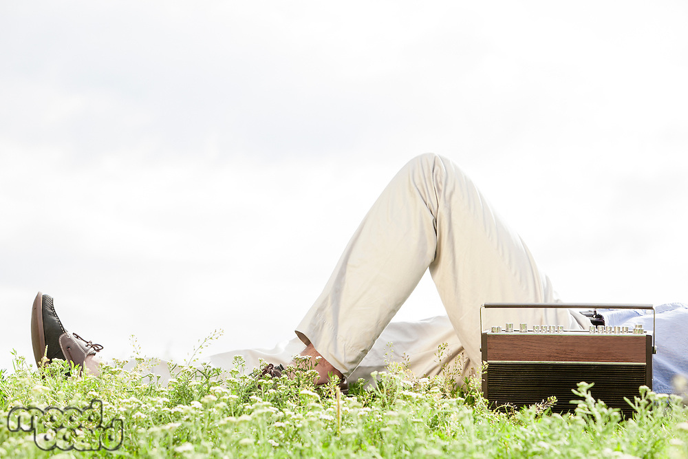 Low section of man lying by vintage radio on grass against clear sky