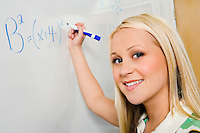 Female student writing equation on whiteboard (portrait)