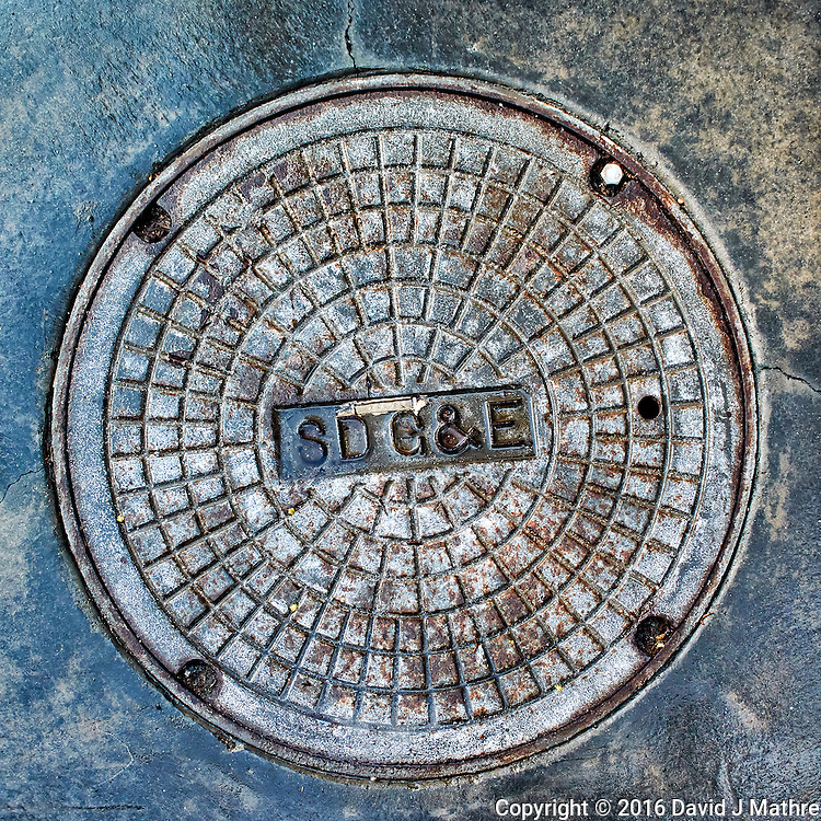 San Diego Gas & Electric manhole cover. Image taken with a Nikon 1 V3 camera and 10 mm VR lens (ISO 200, 10 mm, f/3.5, 1/200 sec).