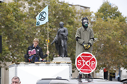 © Licensed to London News Pictures. 07/10/2019. London, UK. An Extinction Rebellion protestor in a gas mask stands on a car during a blockade of Trafalgar Square in central London . Activists are converging on Westminster blockading roads in the area for at least two weeks calling on government departments to 'Tell the Truth' about what they are doing to tackle the Emergency. Photo credit: Peter Macdiarmid/LNP