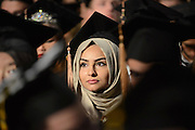 A Kent State graduate waits for graduation ceremonies to start during the Fall 2014 Commencement ceremony.
