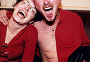 Young man and woman leaning heads together laughing.