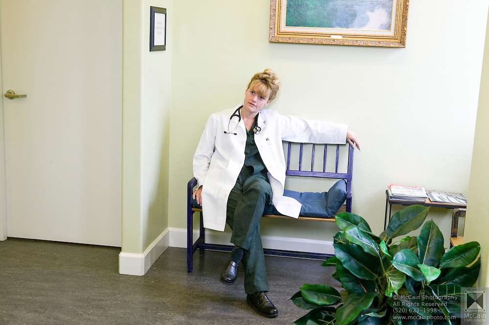Female doctor in white lab coat sitting with legs crossed in the lobby of a medical office, Tucson, Arizona...Media Usage:.Subject photograph(s) are copyrighted Edward McCain. All rights are reserved except those specifically granted by McCain Photography in writing...McCain Photography.211 S 4th Avenue.Tucson, AZ 85701-2103.(520) 623-1998.mobile: (520) 990-0999.fax: (520) 623-1190.http://www.mccainphoto.com.edward@mccainphoto.com