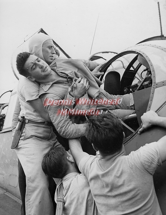 November 1943 - Crewmen lift Kenneth Bratton (AOM - Aviation Ordnance Man) out of the turret of a TBF aboard the USS Saratoga after an air raid on Rabaul.