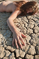 Close-up of a naked woman lying on cracked land