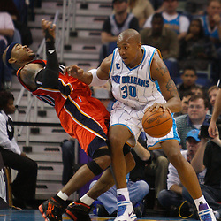 Mar 08, 2010; New Orleans, LA, USA; New Orleans Hornets forward David West (30) draws a charging foul while driving in against Golden State Warriors forward Corey Maggette (50) during the first half at the New Orleans Arena. Mandatory Credit: Derick E. Hingle-US PRESSWIRE