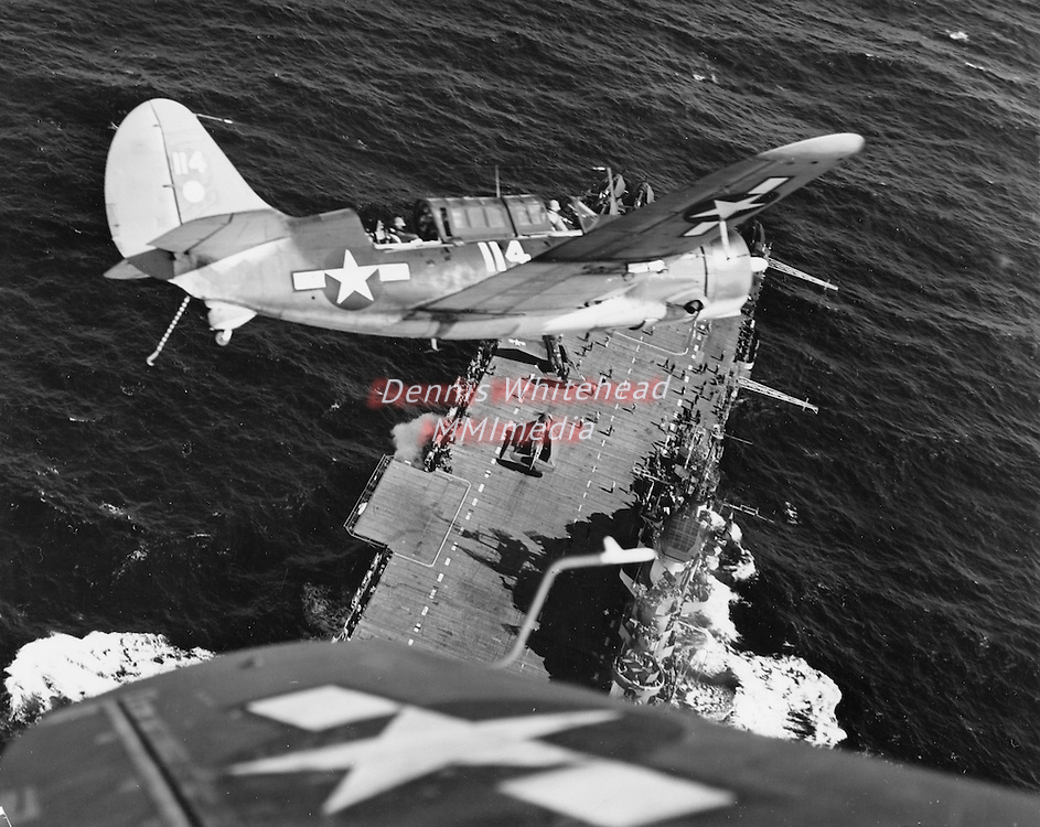 June 1, 1945 - A Navy Curtiss Helldiver is photographed against the background provided by its carrier as it returns from a strike at Japanese shipping. Far below, other planes are being spotted on the flight deck to which the SB2C will soon return.