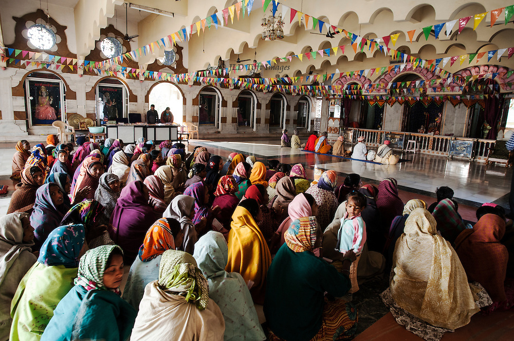 Shree Swaminarayan Temple, Kalupur, Ahmedabad: large group of women seated on the marble floor, a row of men seated in front, chant a meditation.