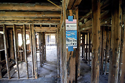 20 August 2015. New Orleans, Louisiana. <br /> Hurricane Katrina revisited. <br /> A decade later and trecovery remains largely elusive for the area hardest hit by Katrina. A sign hangs in an abandoned house offering rebuilding and financing facilities. <br /> Photo credit©; Charlie Varley/varleypix.com.