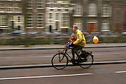 Een man fietst met een kind voorop door Amsterdam.<br /> <br /> A man is cycling with a child at the front of the bike in Amsterdam.