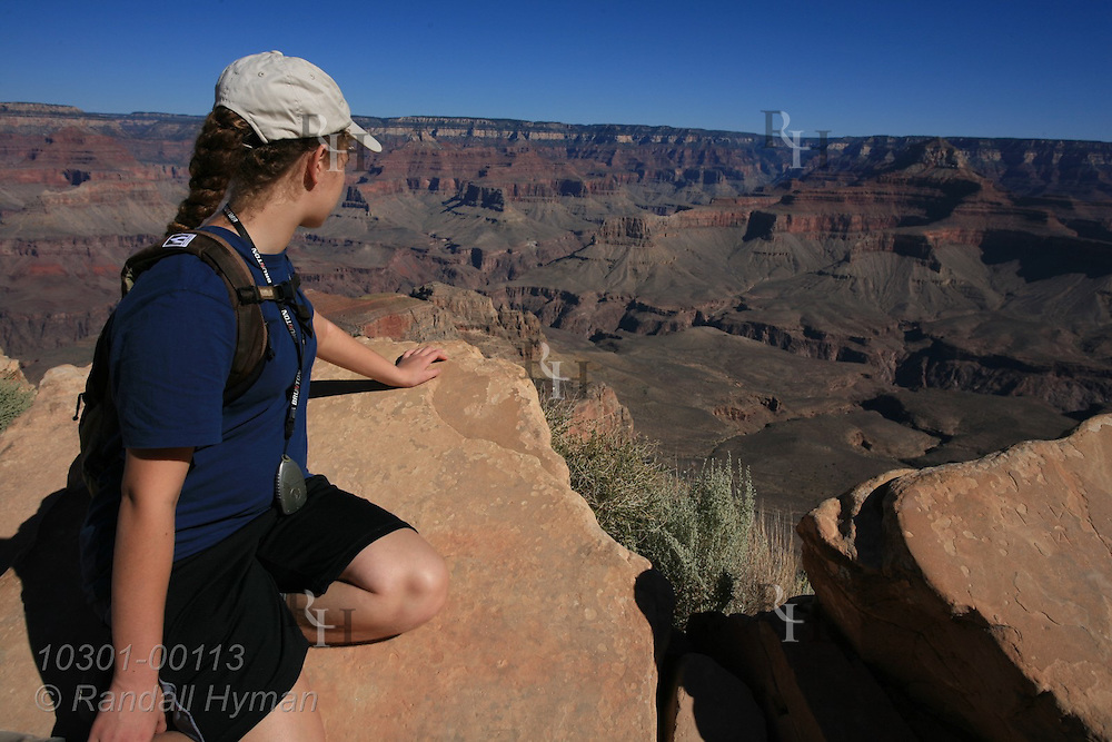 Girl on rock at Ooh-Aah point enjoys sweeping vista from South Kaibab Trail; Grand Canyon National Park, Arizona.