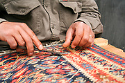fixing a carpet, Marketplace scene, Istanbul, Turkey