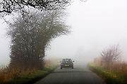 Car on deserted country lane, Gloucestershire, United Kingdom.