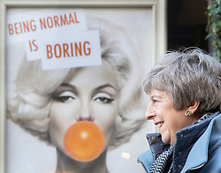 © Licensed to London News Pictures. 04/03/2019. Salisbury, UK. Prime Minister Theresa May emerges from a hairdressers past a poster that says 'Being normal is boring' during a visit to Salisbury on the first anniversary of the poisoning of former Russian spy Sergei Skripal and his daughter Yulia in March 2018. They both survived the nerve agent attack but a resident of nearby Amesbury, Dawn Sturgess, died in June 2018 after coming in contact with the poison. Two Russians have been named in connection with the attack. Photo credit: Peter Macdiarmid/LNP