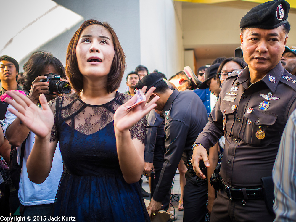 "14 FEBRUARY 2015 - BANGKOK, THAILAND: NATCHACAH KONG-UDOM, left, a Thai democracy advocate, leads a chant in front of a police officer during a protest against the military coup. Dozens of people gathered in front of the Bangkok Art and Culture Centre in Bangkok Saturday to hand out red roses and copies of George Orwell's ""1984."" Protestors said they didn't support either Red Shirts or Yellow Shirts but wanted a return of democracy in Thailand. The protest was the largest protest since June 2014, against the military government of General Prayuth Chan-Ocha, who staged the coup against the elected government. Police made several arrests Saturday afternoon but the protest was not violent.    PHOTO BY JACK KURTZ"