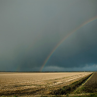 Regenboog over de polder. Rainbow coming out of the clouds.