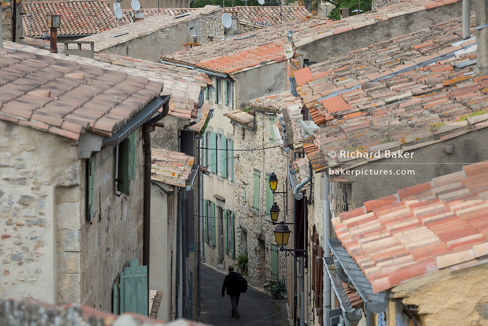 A single figure walks between houses each side of narrow medieval streets, on 22nd May, 2017, in Lagrasse, Languedoc-Rousillon, south of France. Lagrasse is listed as one of France's most beautiful villages and lies on the famous Route 20 wine route in the Basses-Corbieres region dating to the 13th century.