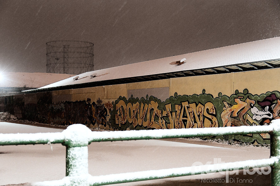 During a night snowfall, the silhouette of the gazometro appears in the distance behind the buildings of the former slaughterhouse in Testaccio, Rome
