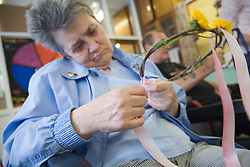 Woman weaving with willow in a natural arts and crafts session run by Groundworks day centre,