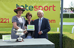 Left to right, MRS PETER JONES presents WENDY BUSH representing the owners of Unshakakle the tropy for winning the Totesport Mile with the trainer BOB JONES at the 4th day of the 2005 Glorious Goodwood horseracing festival at Goodwood Racecourse, West Sussex on 29th July 2005.    <br />