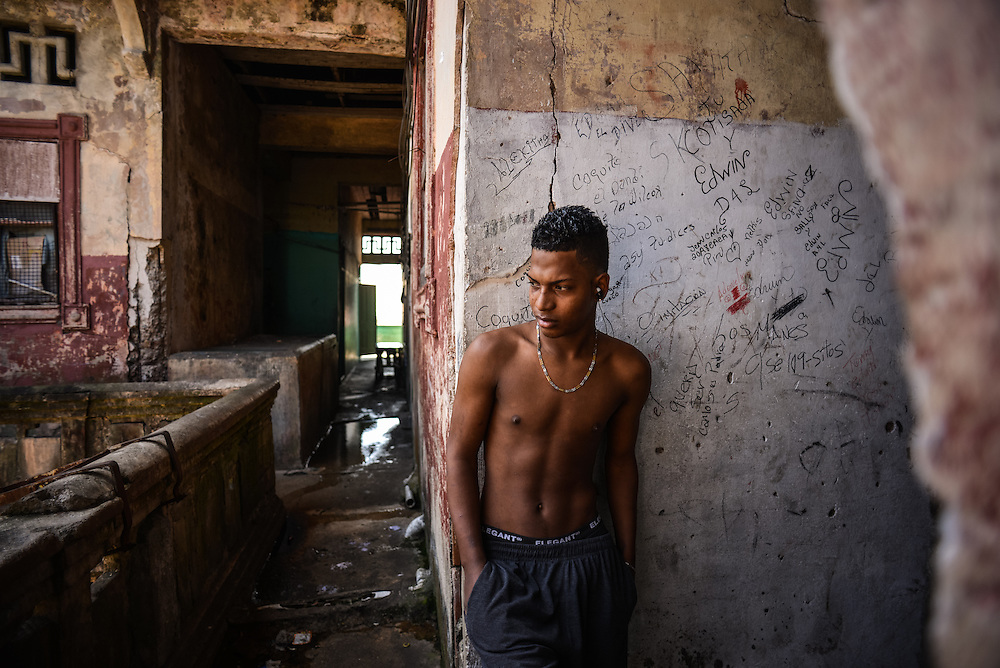 A squatter listens to music near the space where he lives inside the Wilcox building, with pools of run-off sewage in the hallways behind him.  The Wilcox building was once an architectural landmark in Colón, but is now a condemned building, notorious for being a violent crime hub in the city, with over 100 squatters living inside. Despite being the second largest city in Panama, Colón is one of the poorest in the region, and its residents suffer from a critical shortage of potable water, sewer connections and housing--many people live in condemned or should be condemned buildings. Panama is now one of the fastest growing countries in Latin America and there is a growing resentment and impatience that Colón has not reaped as much of the benefit as Panama City.