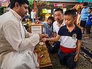 31 AUGUST 2014 - SARIKA, NAKHON NAYOK, THAILAND: A Thai boy gets a blessed string from a Hindu priest at the Ganesh festival at Shri Utthayan Ganesha Temple in Sarika, Nakhon Nayok. Ganesh Chaturthi, also known as Vinayaka Chaturthi, is a Hindu festival dedicated to Lord Ganesh. It is a 10-day festival marking the birthday of Ganesh, who is widely worshiped for his auspicious beginnings. Ganesh is the patron of arts and sciences, the deity of intellect and wisdom -- identified by his elephant head. The holiday is celebrated for 10 days, in 2014, most Hindu temples will submerge their Ganesh shrines and deities on September 7. Wat Utthaya Ganesh in Nakhon Nayok province, is a Buddhist temple that venerates Ganesh, who is popular with Thai Buddhists. The temple draws both Buddhists and Hindus and celebrates the Ganesh holiday a week ahead of most other places.    PHOTO BY JACK KURTZ