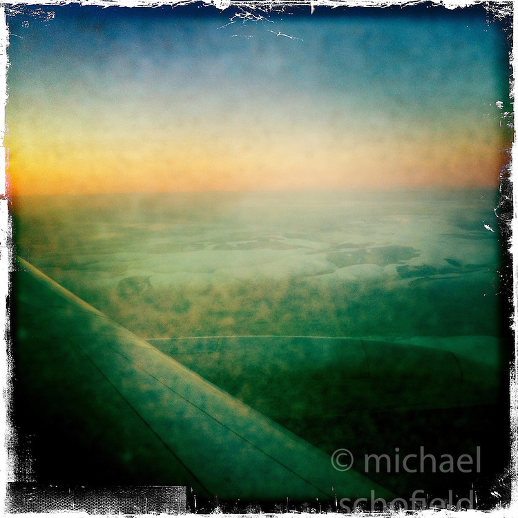 Aircraft wing in flight..Hipstamatic images taken on an Apple iPhone..©Michael Schofield.