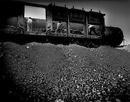 Workers shovel soil out of a train car to the side of the tracks, near Wuhai, Inner Mongolia Autonomous Region, China.