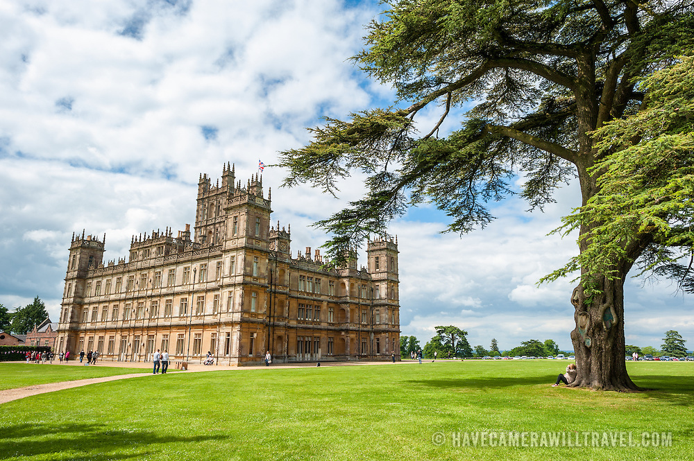 Highclere Castle Grounds with Tree. Highclere Castle, in Hampshire, is the home of the Earl and Countess of Carnarvon and is used in the filming of the British TV series Downton Abbey.