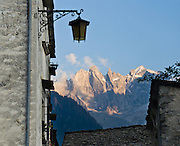 Sunset light hits rugged granite mountains of Sciora Group in the Bregaglia Range, Soglio village, Bregaglia Valley, Graubünden (Grisons) canton, Switzerland, the Alps, Europe.