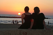 A silhouette of a romantic couple watching the sun set