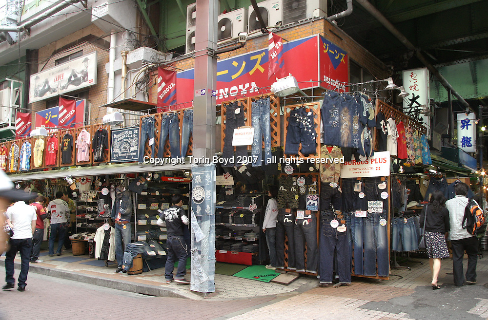 This is Hinoya, a popular clothing store in Tokyo that sells vintage blue jeans, Hawaiian shirts and various other casual wear. The proprietor of this establishment is Koji Miura and Hinoya is his main outlet. Located in Okachimachi, a bustling market area famous for cheap food and clothing stores, as well as seedy but atmospheric restaurants, this district is one of the few remnants of Occupied Japan left in Tokyo. Some of the items for sale at Hinoya are rare vintage American blue jeans from the 1930s, 1940s, and 1950s, many of them in original unused condition ranging in price from $100 to $350. This view shows the exterior of the shop.