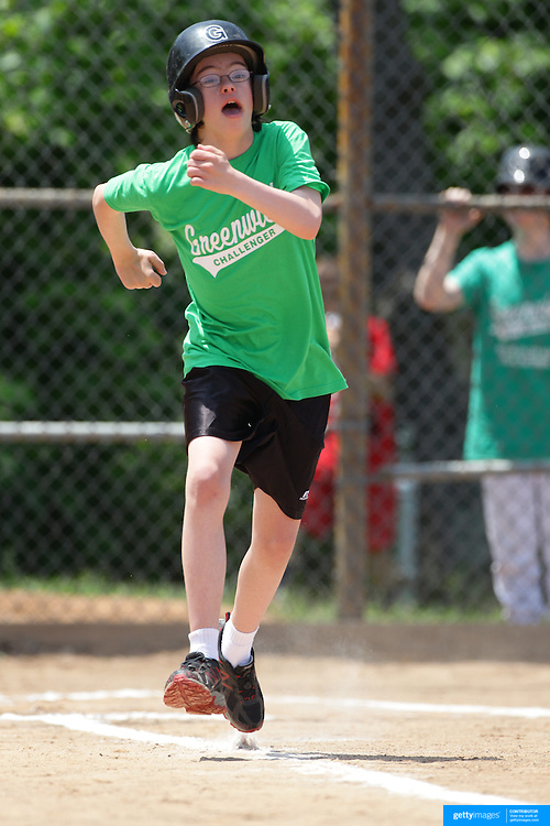 A batter celebrates at first base after a hit during the Norwalk Little League baseball 'Champions' team V Greenwich in the Challenger Division  Recognition Day competition. The day acknowledged the many talents of the great players on the Challenger Division teams. The division has weekly games and practices for kids with special needs. Challenger division are held throughout the country.  Broad River Fields, Norwalk, Connecticut. USA. 2nd June 2013. Photo Tim Clayton