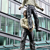 """Two Men Sculpture by Stephan Balkenhol in Mainz, Germany <br /> Stephan Balkenhol is a German sculptor whose wooden carvings typically depict stylized people in interesting poses. This outdoor statue of acrobats is called """"Two Men"""" and was created in 2001. The artwork is located at the corporate headquarters of Westdeutsche Immobilien Servicing AG. WestImmo specializes in financing for commercial real estate."""