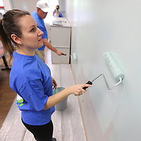 Heather Parker, a district coordinator for Sherwin Williams, uses a roller to paint one of the walls in the kitchen at the Family Resource Center in Tupelo on Tuesday morning.