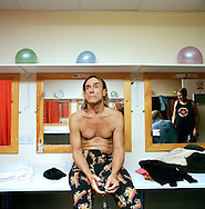 Iggy Pop relaxing backstage with a glass of red wine.