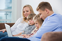 Parents with children using laptop on sofa at home