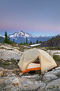 Tent in backcountry campsite. Yellow Aster Butte Basin, Mount Baker Wilderness. Mount Shuksan is in the distance. North Cascades Washington