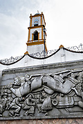 The Church of Nuestra Senora de la Asuncion peaks up from behind the massive sculpture: Evolution of the Totonac culture by Teodoro Cano Garcia, in the Plaza Central Israel Tellez Park in Papantla, Veracruz, Mexico.