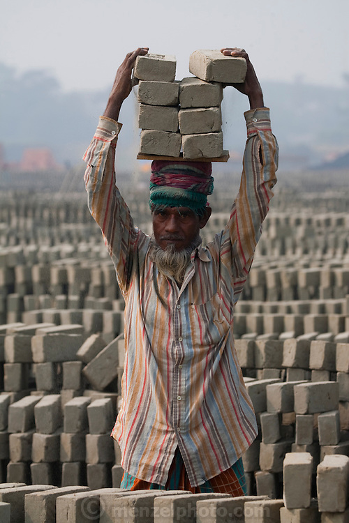 A factory worker carries a stack of bricks at the JRB brick factory near Sonargaon, outside Dhaka, Bangladesh. The heavy clay soils along the river near the market town of Sonargaon are well suited for making bricks. At the JRB brick factory, workers of all ages move raw bricks from long, stacked rows, where they first dry in the sun, to the smoky coal-fired kilns. After being fired, the bricks turn red. A foreman keeps tally, handing the workers colored plastic tokens corresponding to the number of bricks they carry past him. They cash in the chips at the end of each shift, taking home the equivalent of $2 to $4 (USD) a day.