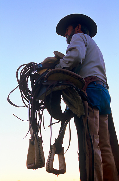cowboy standing with his saddle and eqiupment