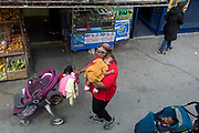 A lady carries a child past a fruit and vegetable shop in Camberwell, Southwark, on 18th June 2019, in London, England.