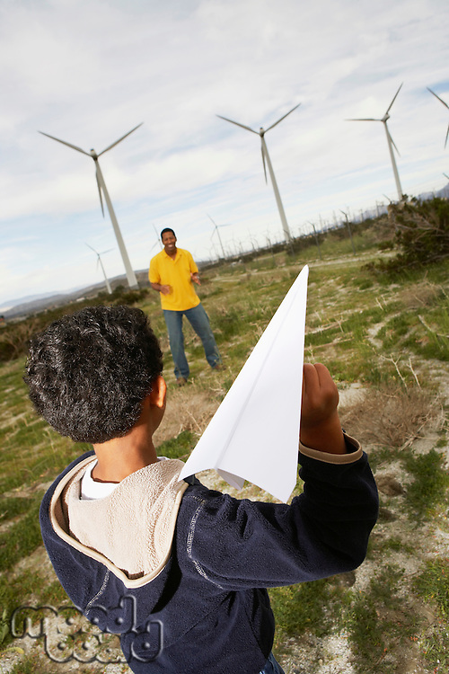 Father and son (7-9) playing with paper plane at wind farm