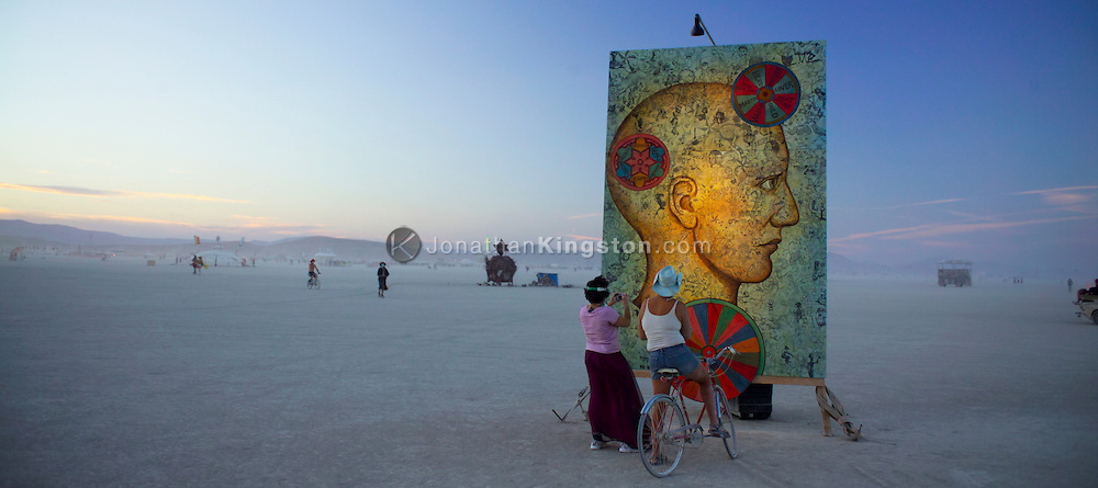 "BLACK ROCK CITY, NV:  Two Burning Man participants examine a art piece called ""Head Games"" by Lisa Beerntsen, Tony Speirs and Easel Park Sketchers of Graton, CA in Black Rock City, Nevada."