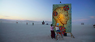 """BLACK ROCK CITY, NV:  Two Burning Man participants examine a art piece called """"Head Games"""" by Lisa Beerntsen, Tony Speirs and Easel Park Sketchers of Graton, CA in Black Rock City, Nevada."""