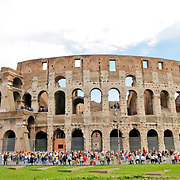 At daytime shot of Rome's famous Coliseum, with crowds of tourists milling arounds its base.